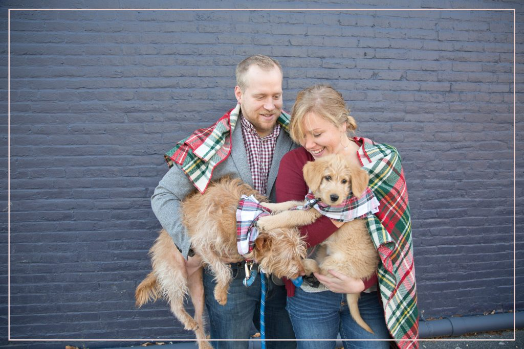 family session. Couple candidly posing with two puppies.