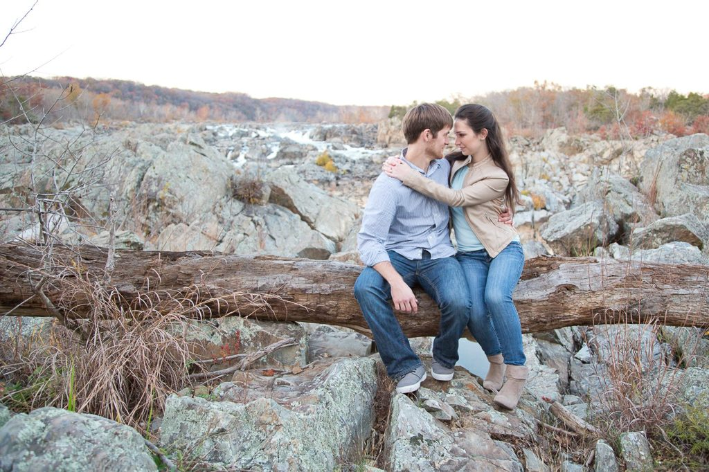 couple hugging and sitting on log over great falls
