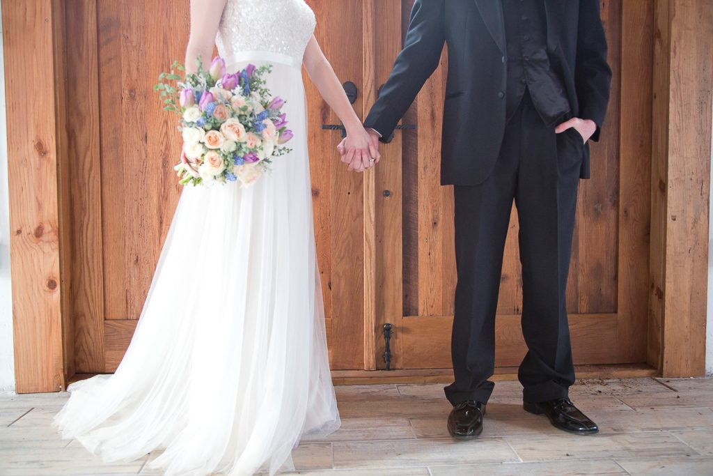 bride and groom hold hands by wooden doors