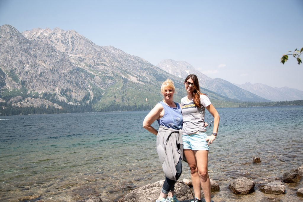 ladies smiling for photo with lake in background