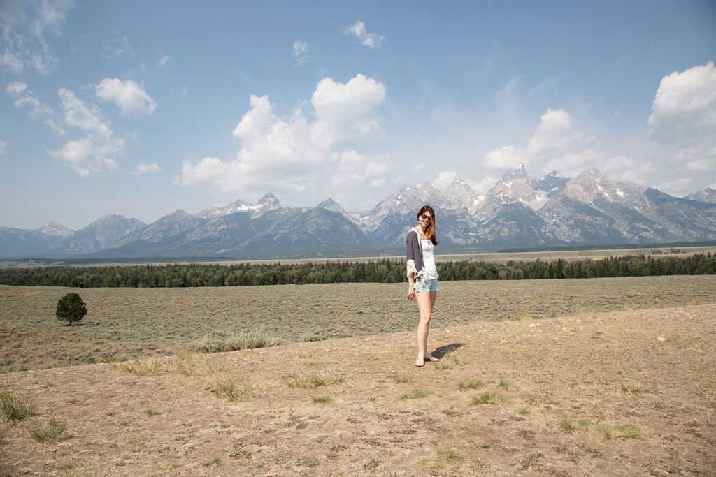 lady in sunglasses with Teton mountains behind her
