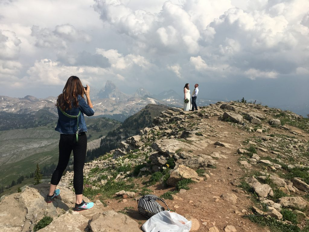 lady photographing wedding couple on mountain top