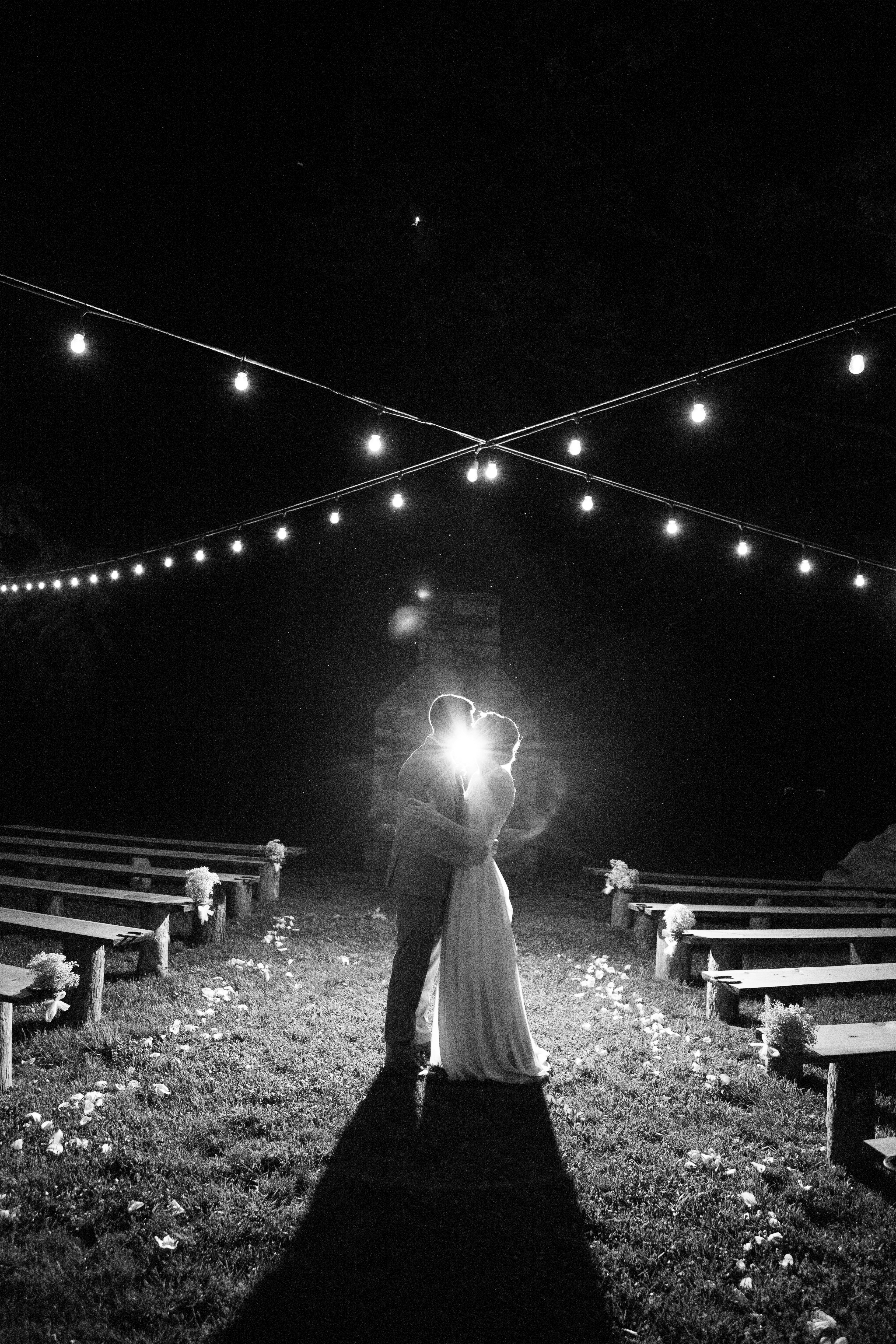 night time photo of couple kissing under bistro lights