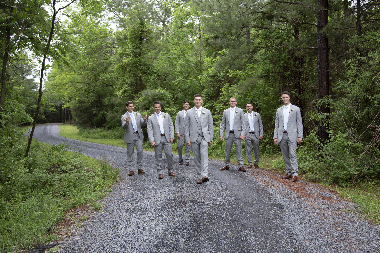 groom and groomsman walking down gravel road in grey suits