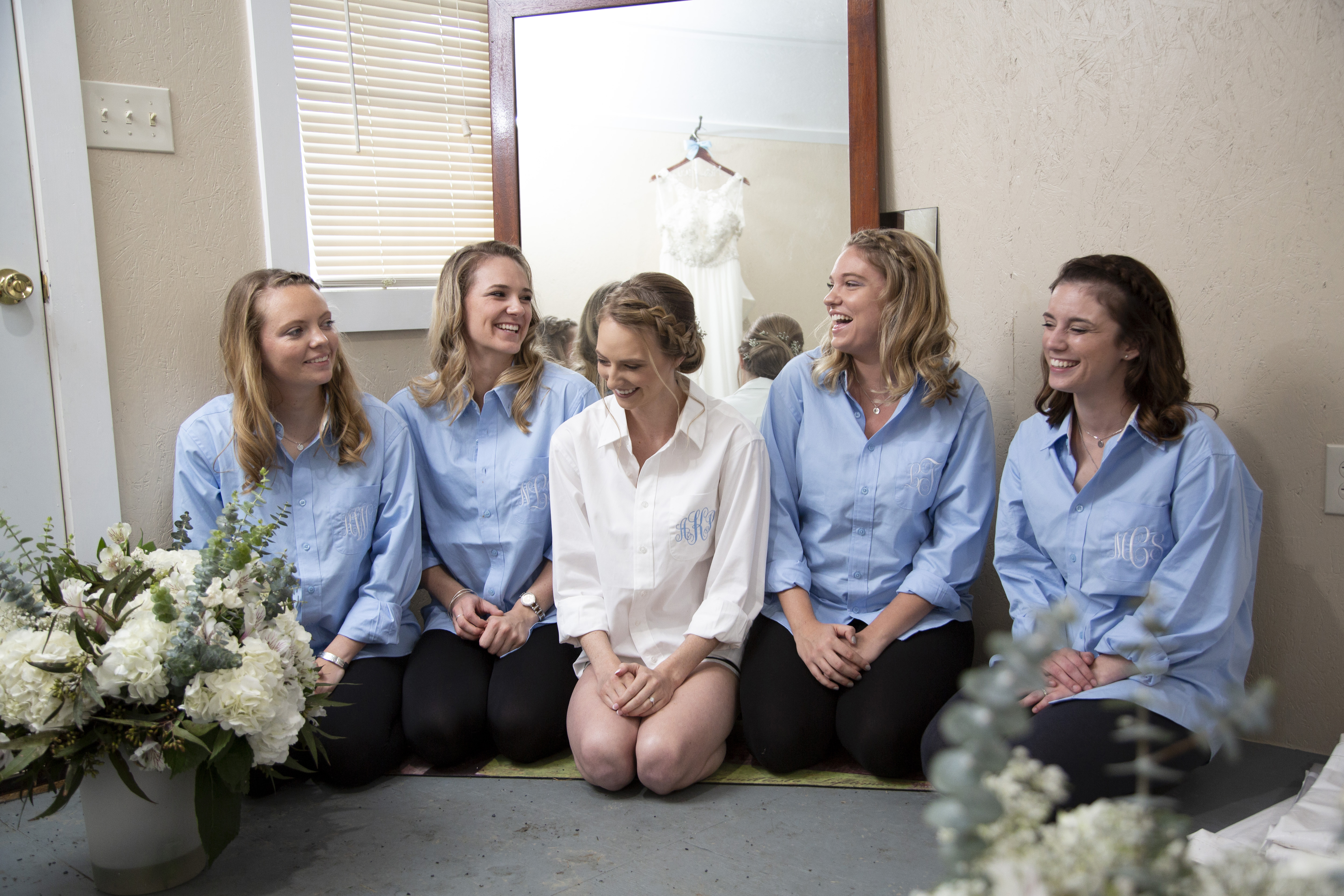 bride and bridesmaids laughing and wearing matching shirts