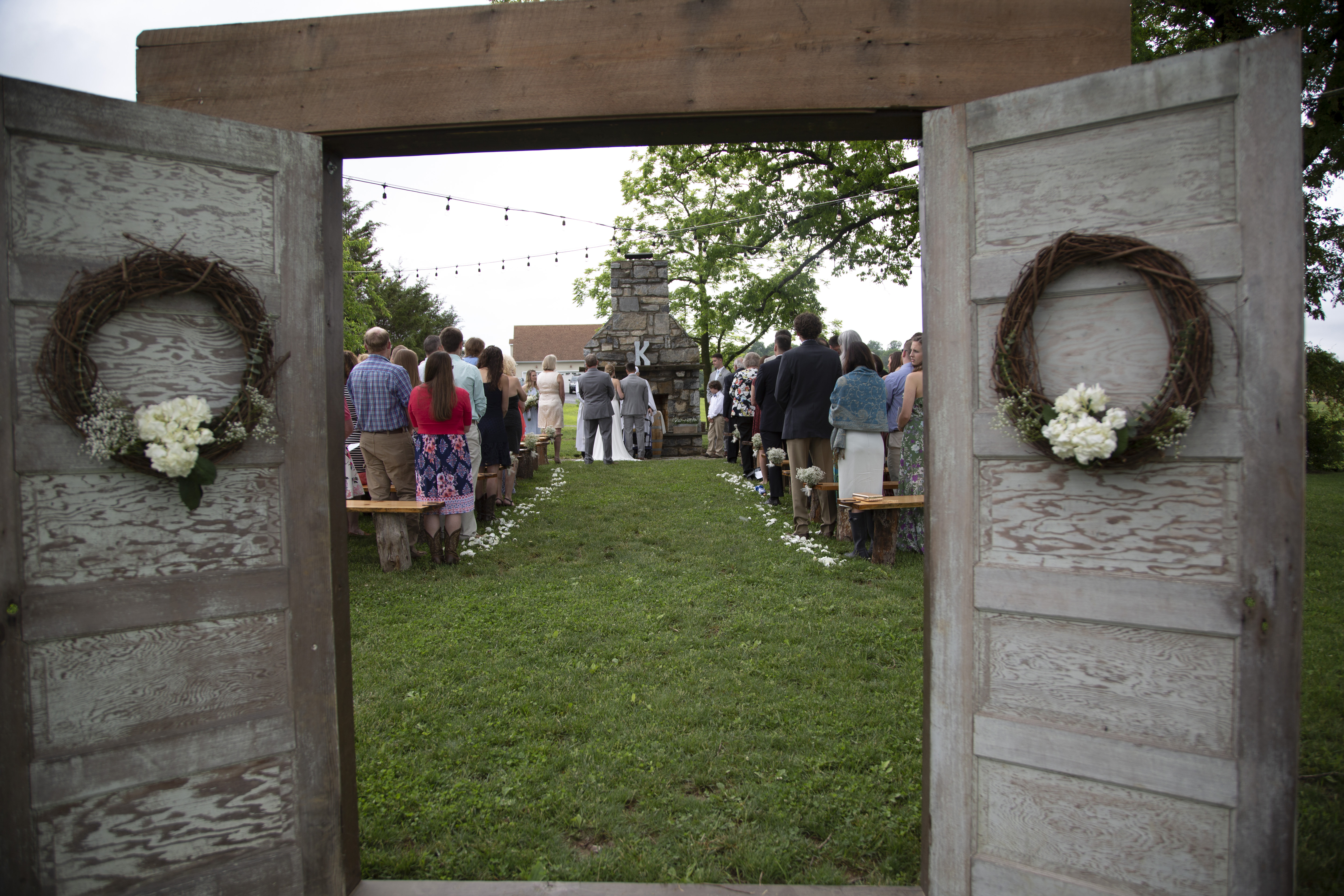 outdoor rustic wedding ceremony with vintage door arch