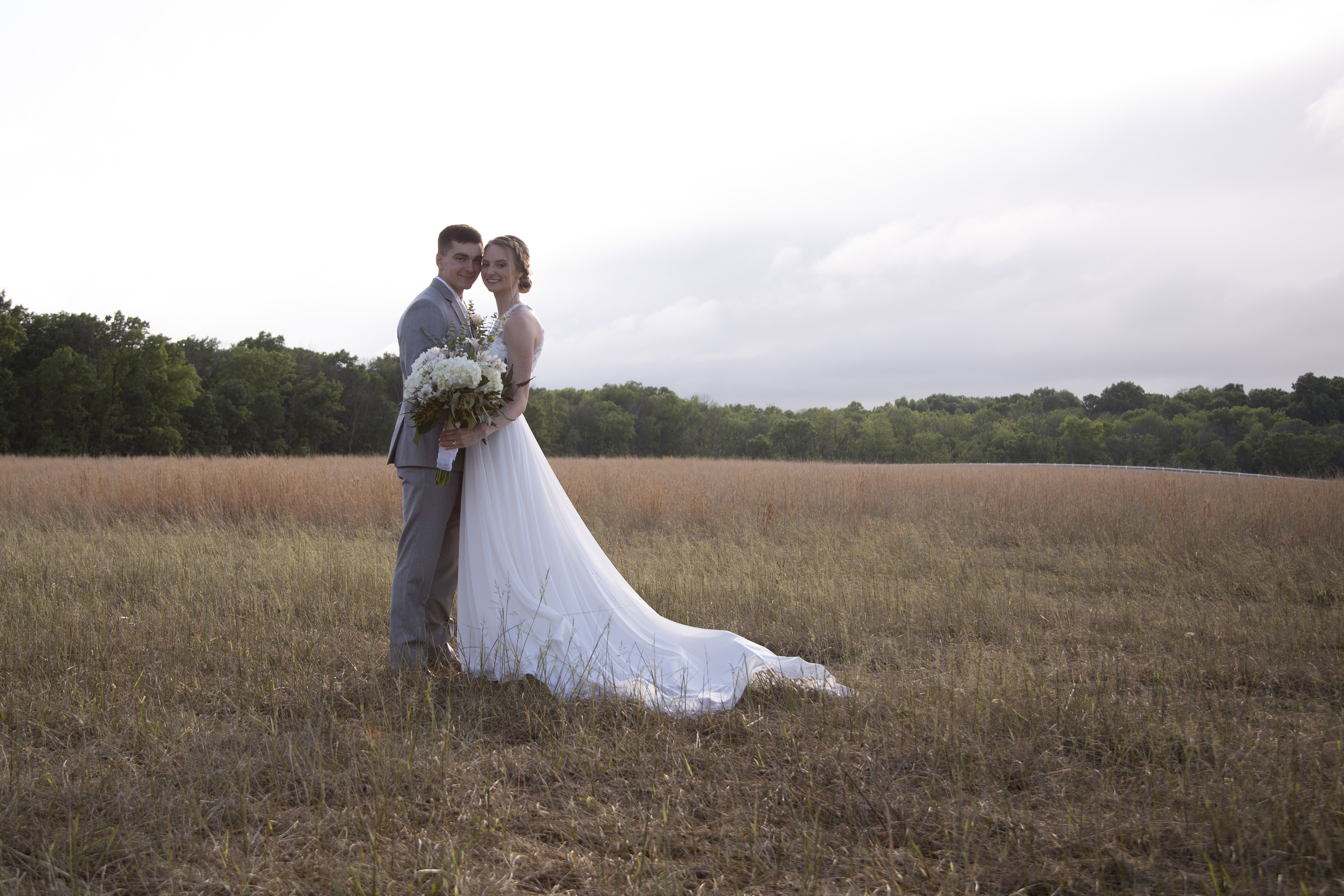 couple in open field at sunset