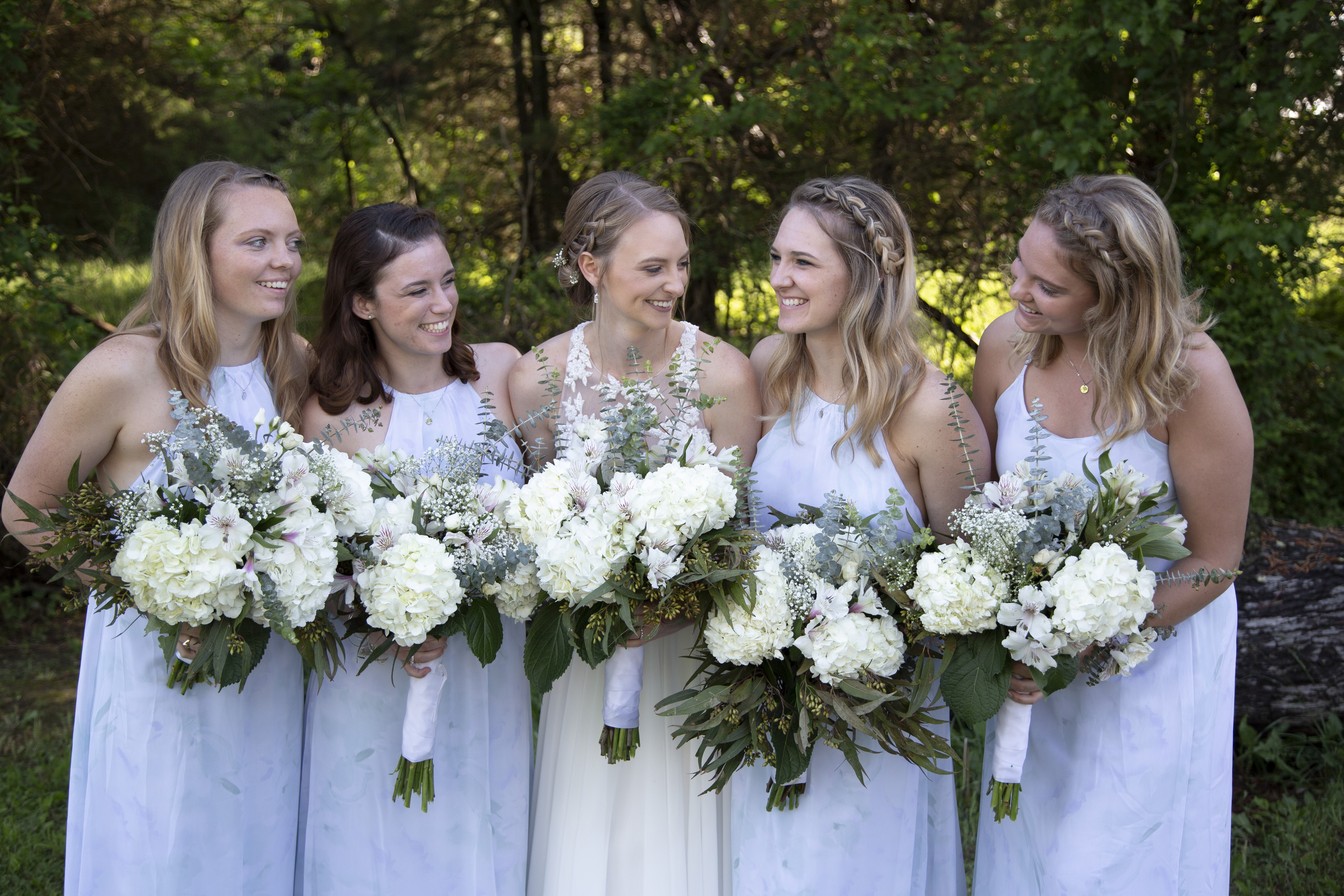 bride and bridesmaids smiling and holding bouquets