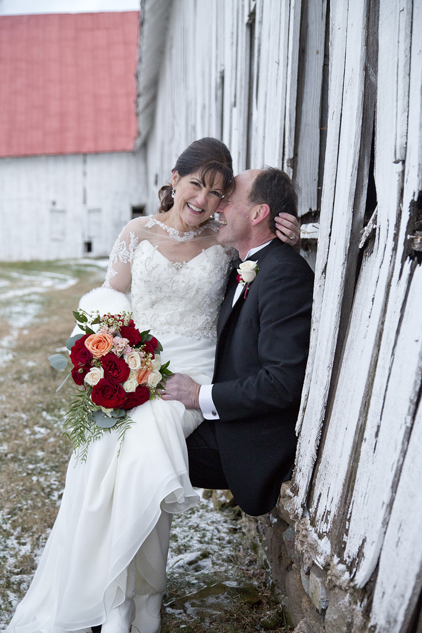 bride and groom embracing by barn in the snow