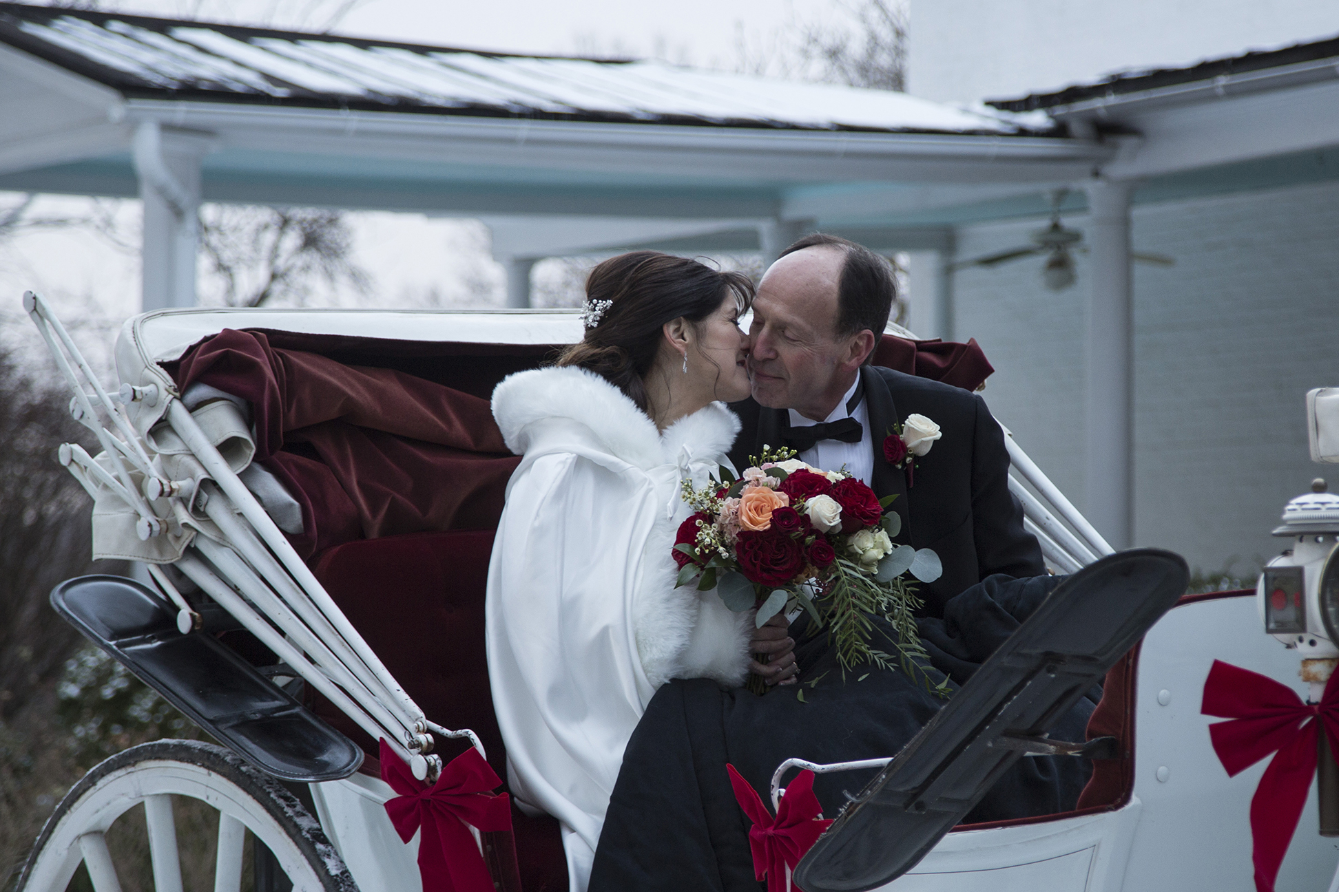 bride and groom kissing on carriage