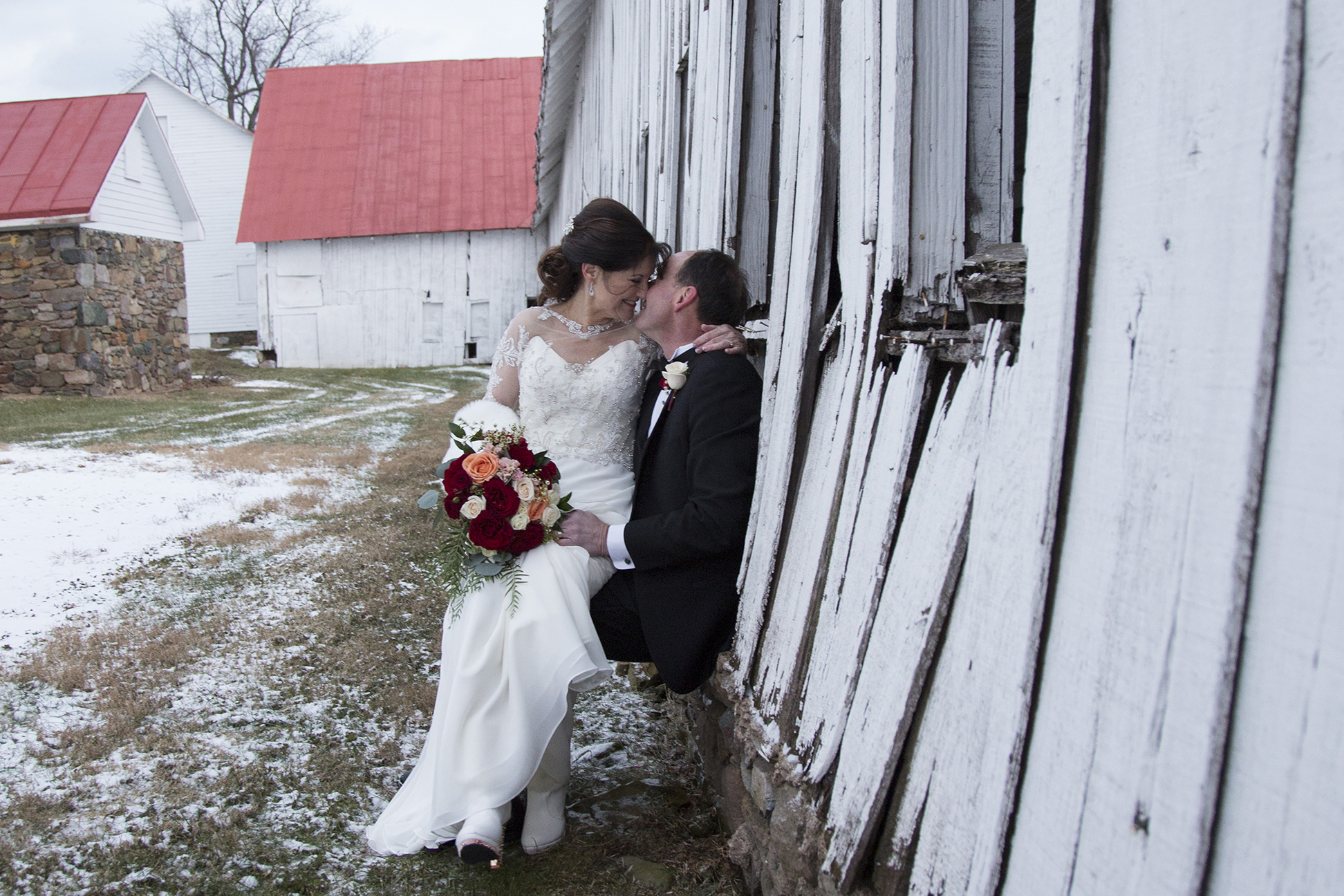Bride and groom kissing by barn in the snow
