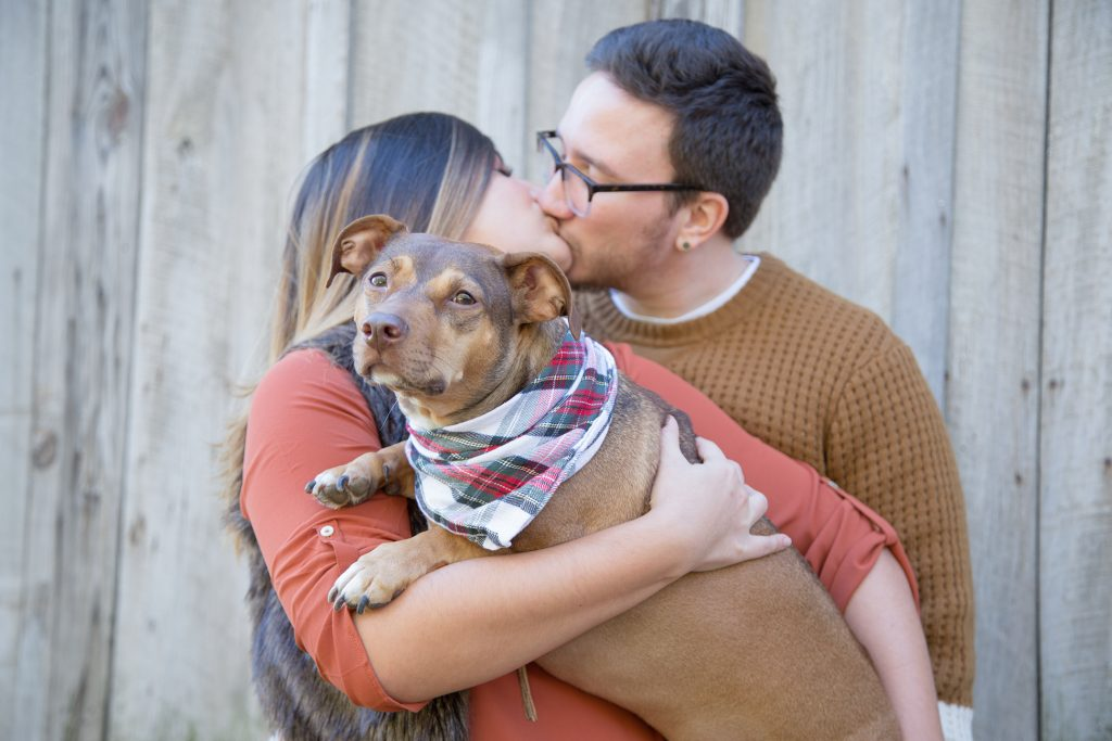 couple kissing while holding dog in bandana