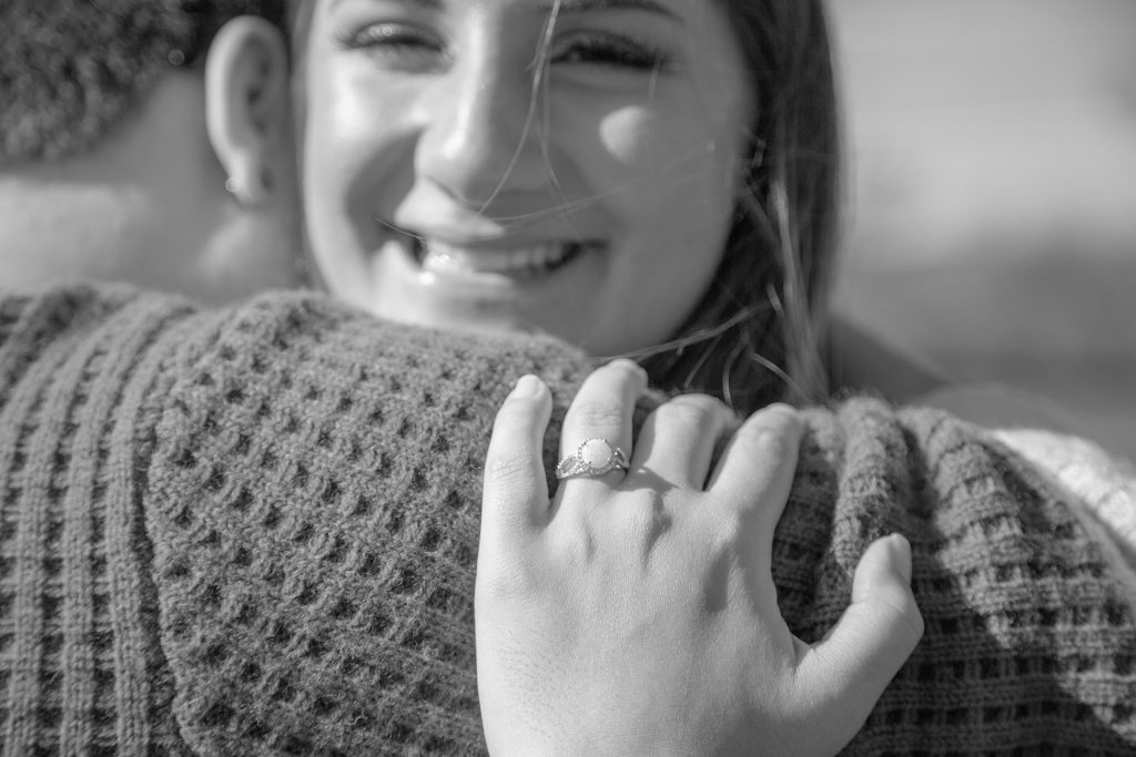 close up of engagement ring with women smiling in background after surprise proposal