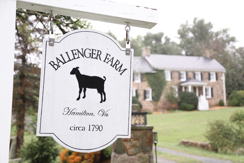 farm sign with house in background