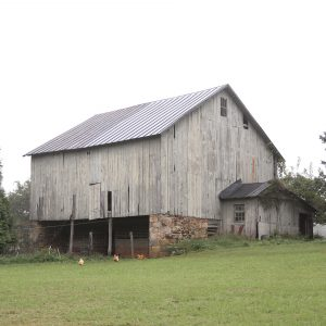 rustic barn with chickens in front of it