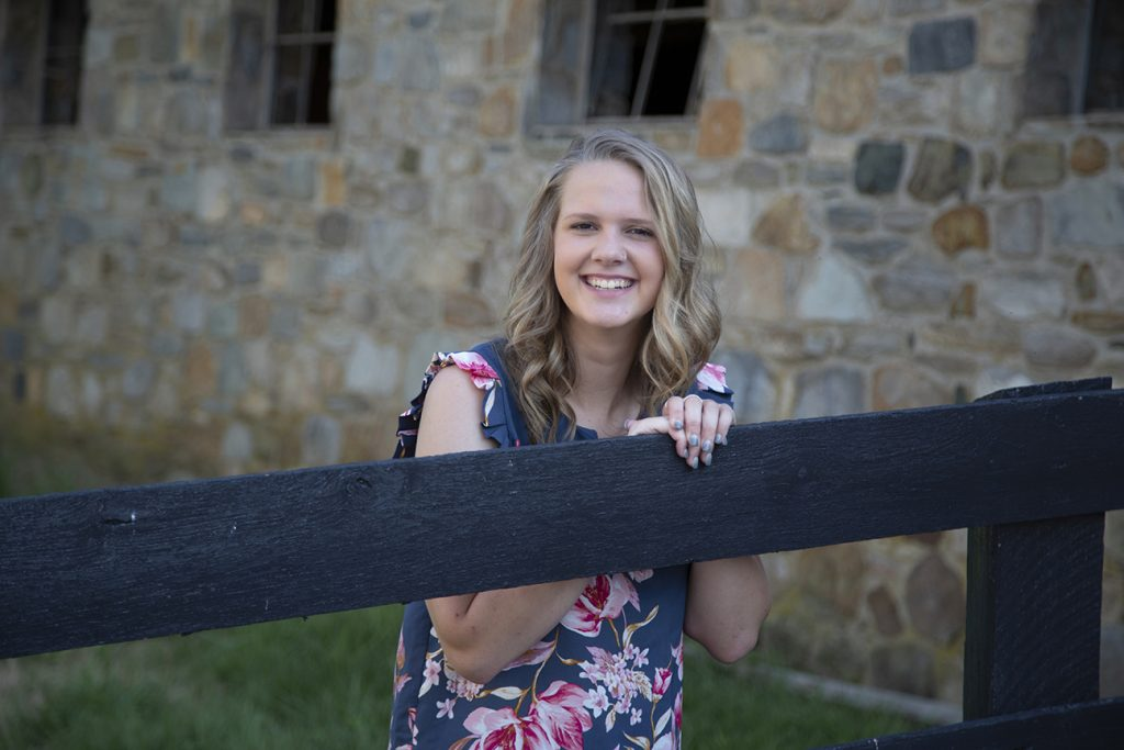 teenage girl standing by fence and barn