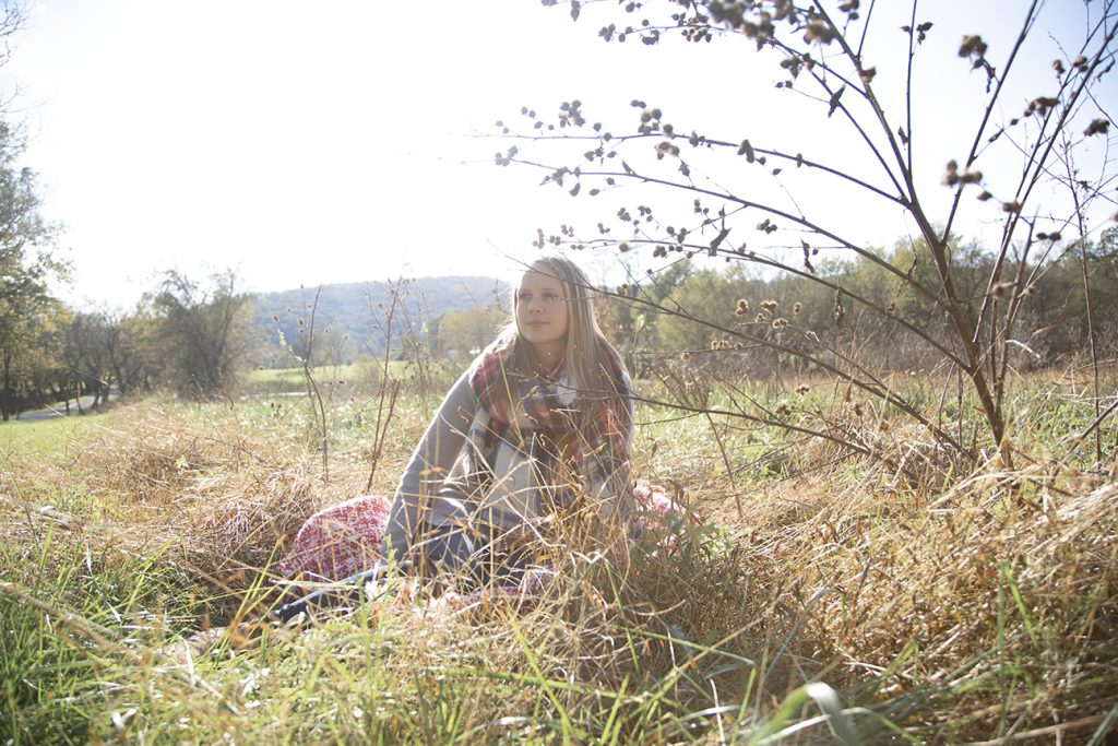 teenage girl sitting in field during fall