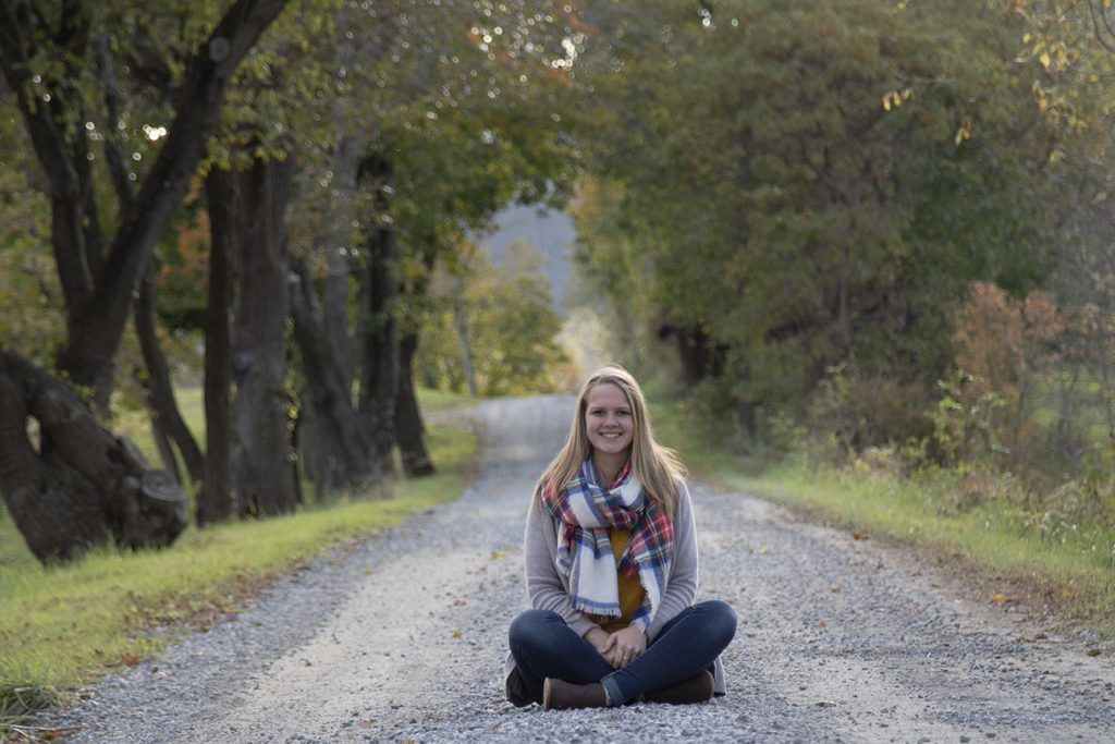 teenage girl sitting in middle of dirt road