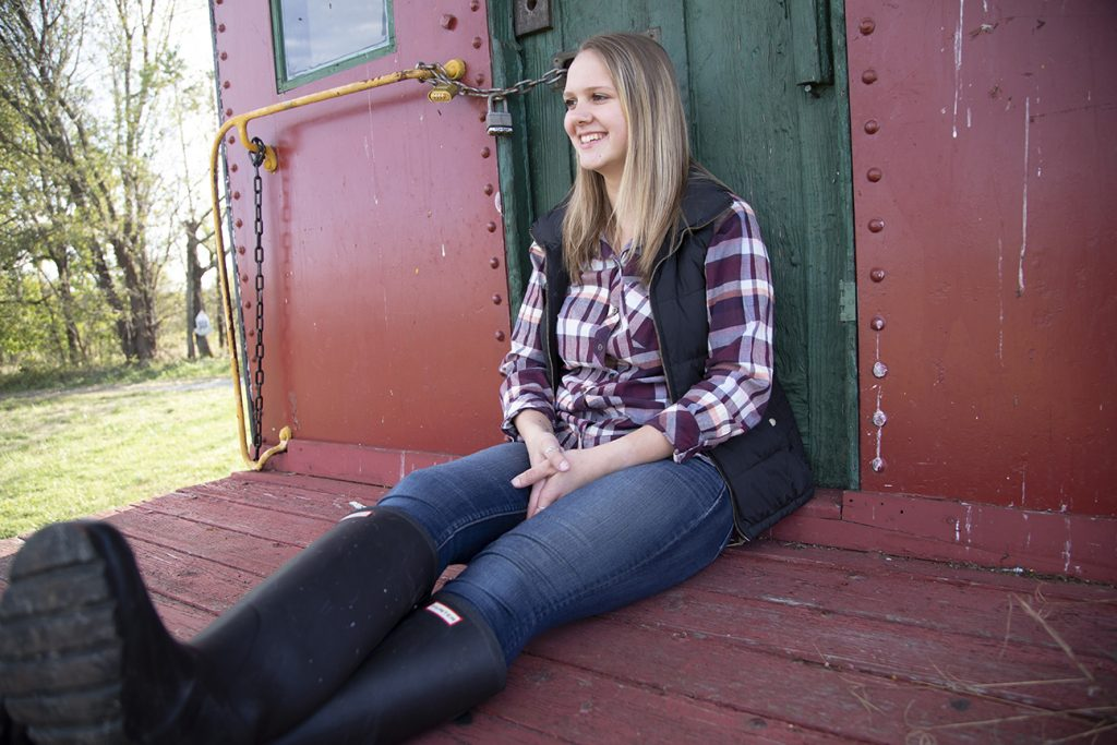 teenage girl sitting on back of caboose
