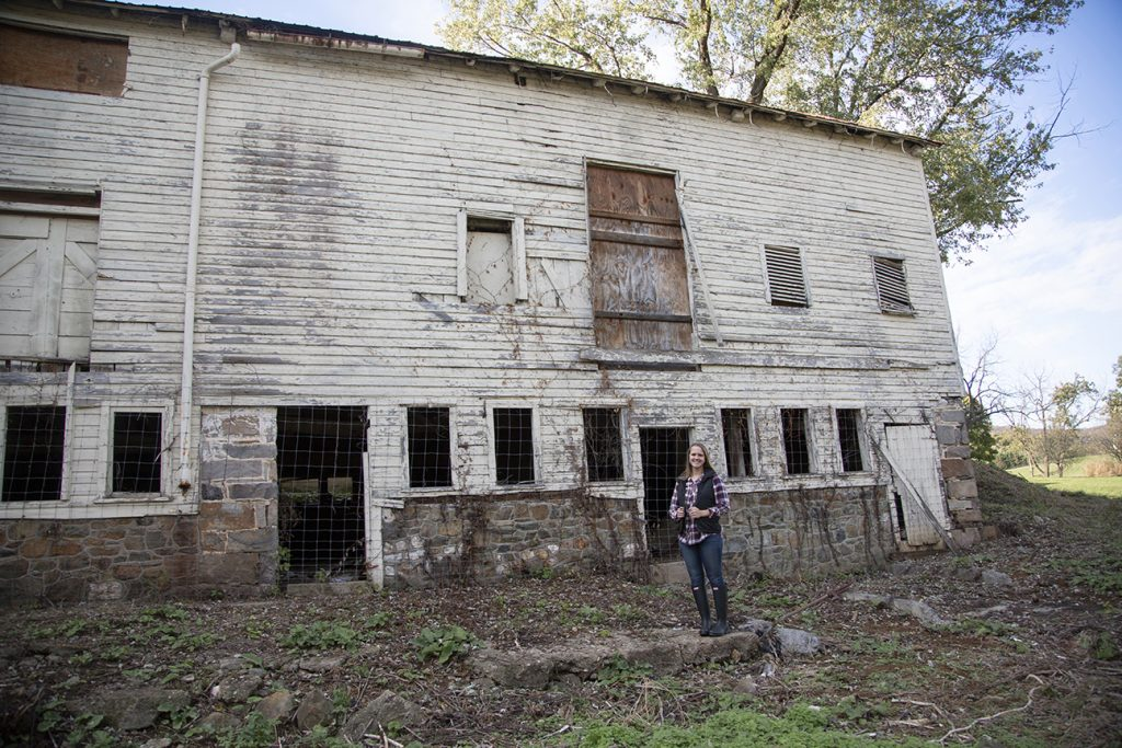 teenage girl standing by barn