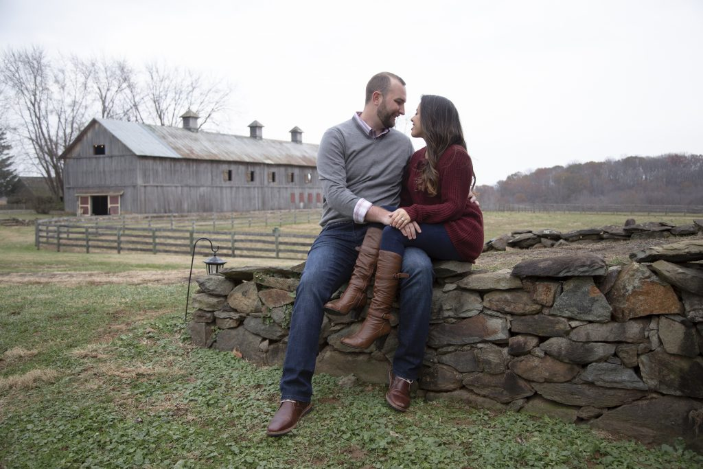 couple sitting on stone wall with barn in background