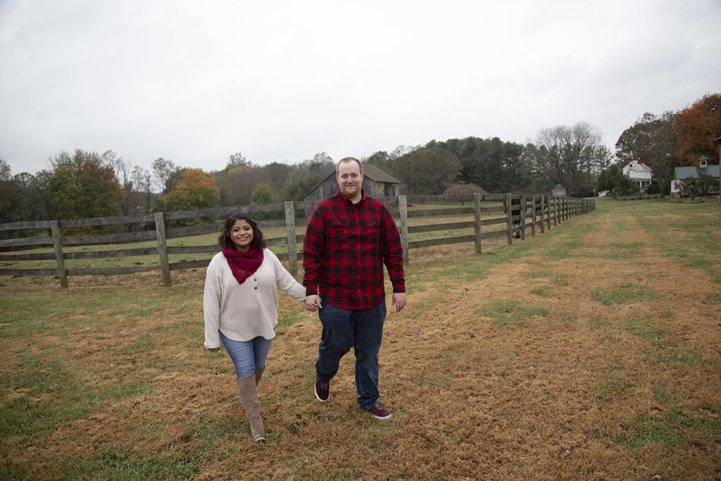 engaged couple walking hand in hand by horse fence
