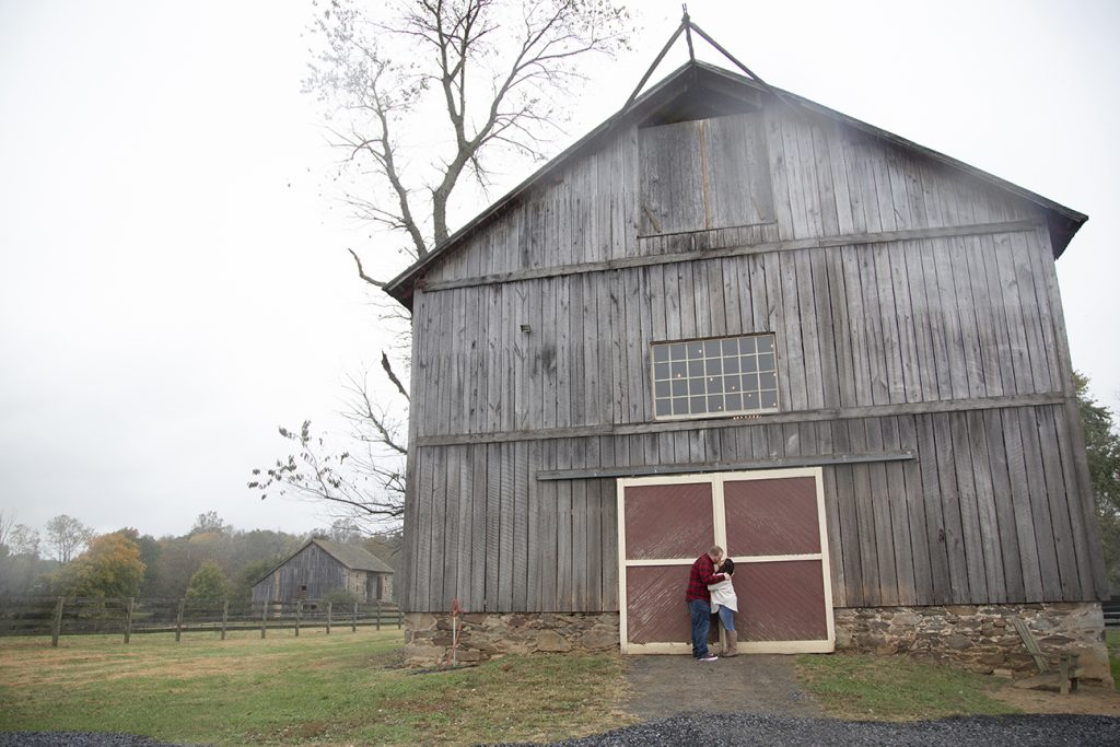 couple kissing y rustic barn