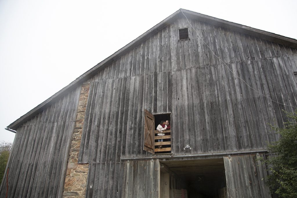 engagement couple kissing in barn window