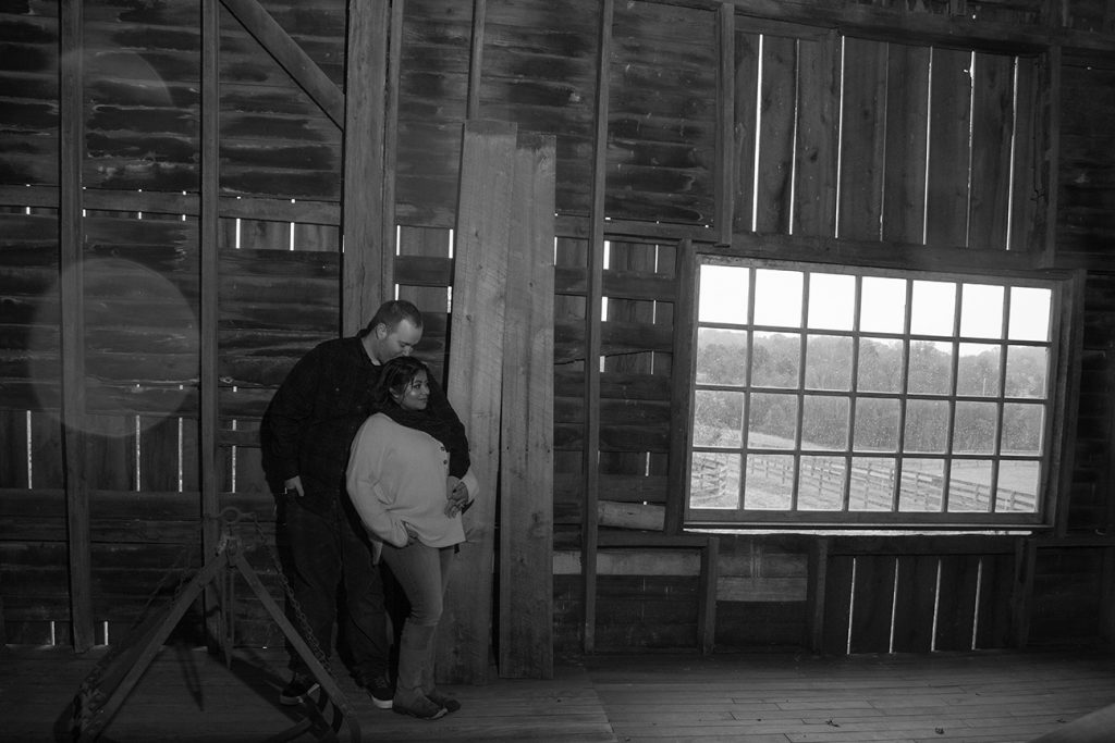 engagement couple embracing in barn