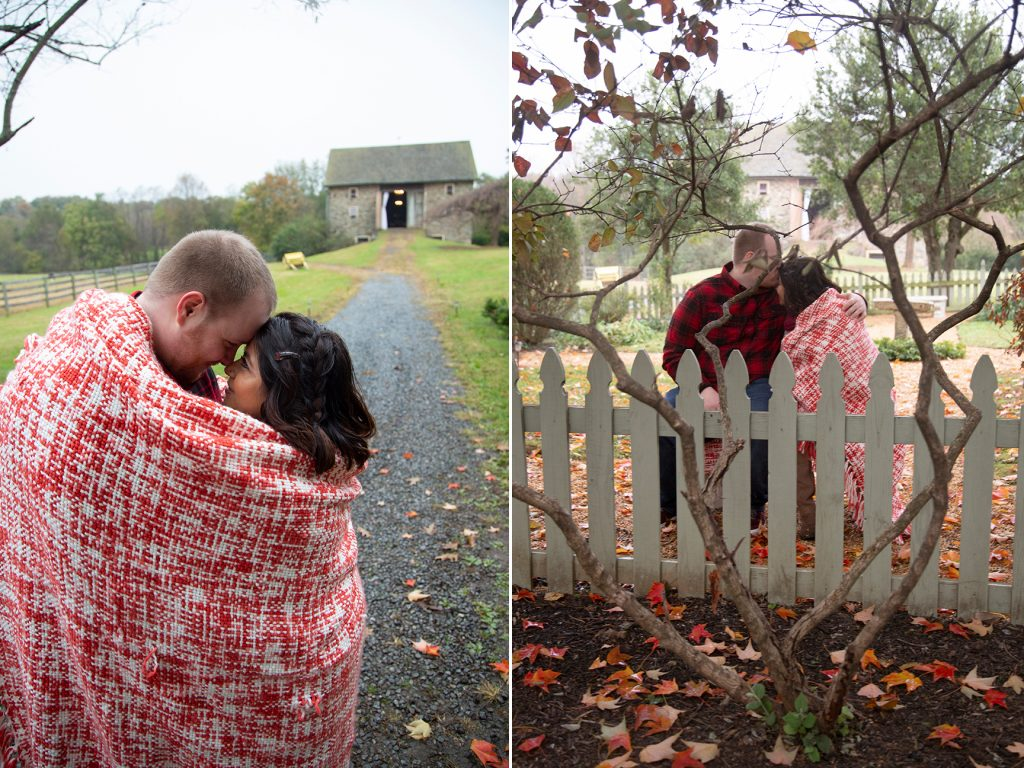 engaged couple embracing by barn