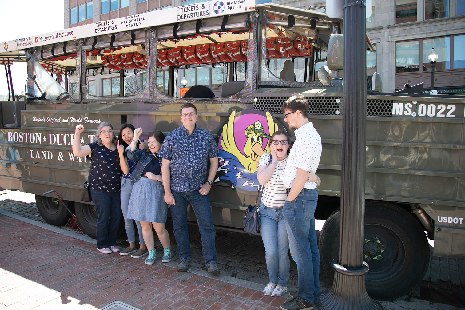 family posing by duck boat