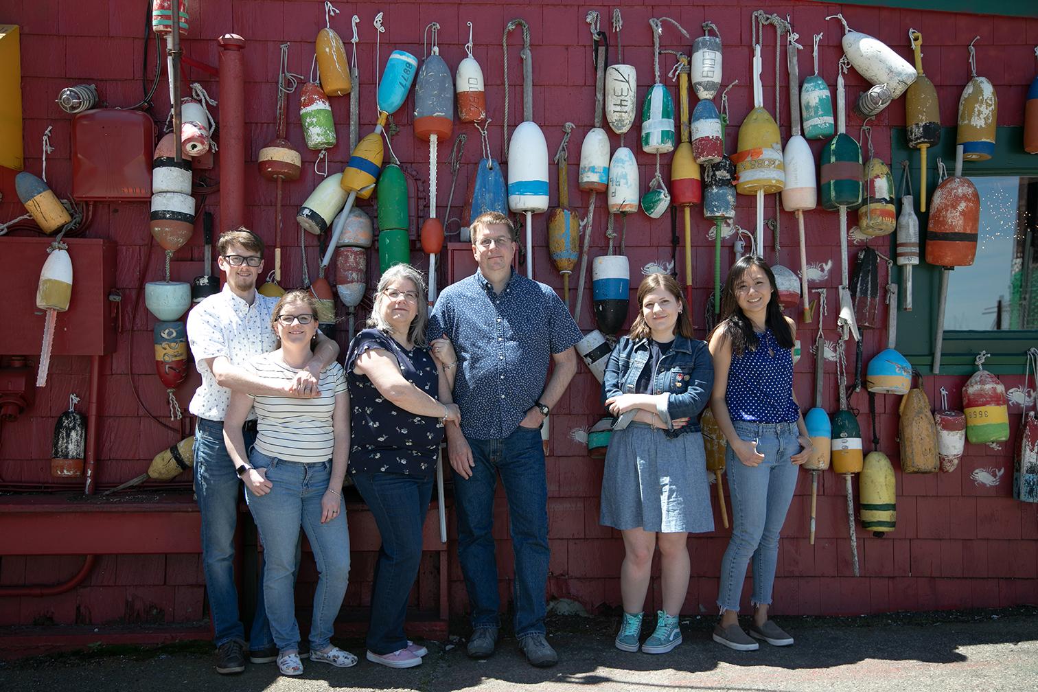 family posing on buoy wall