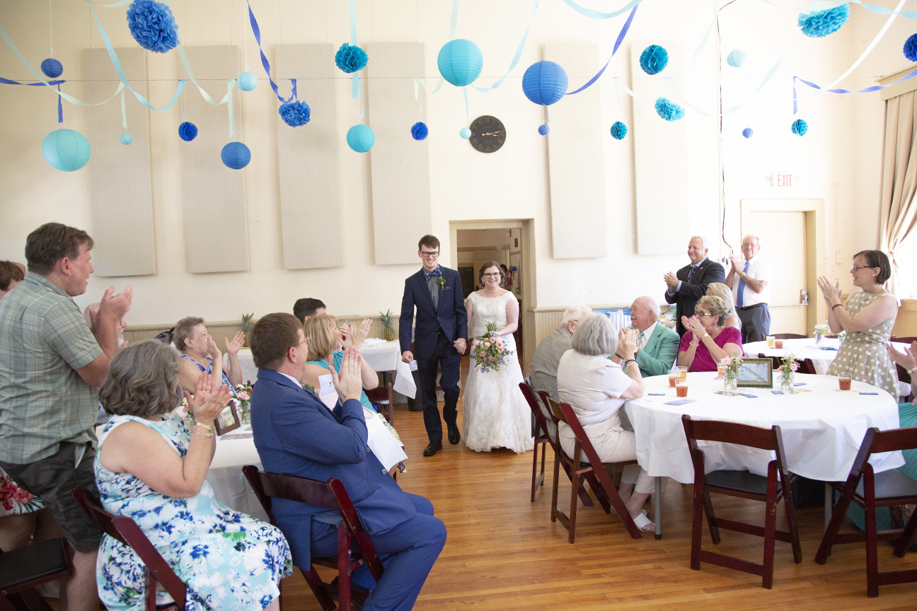 couple enters reception at old stone school