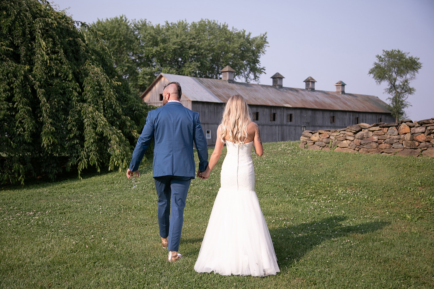 couple walking with barn in background