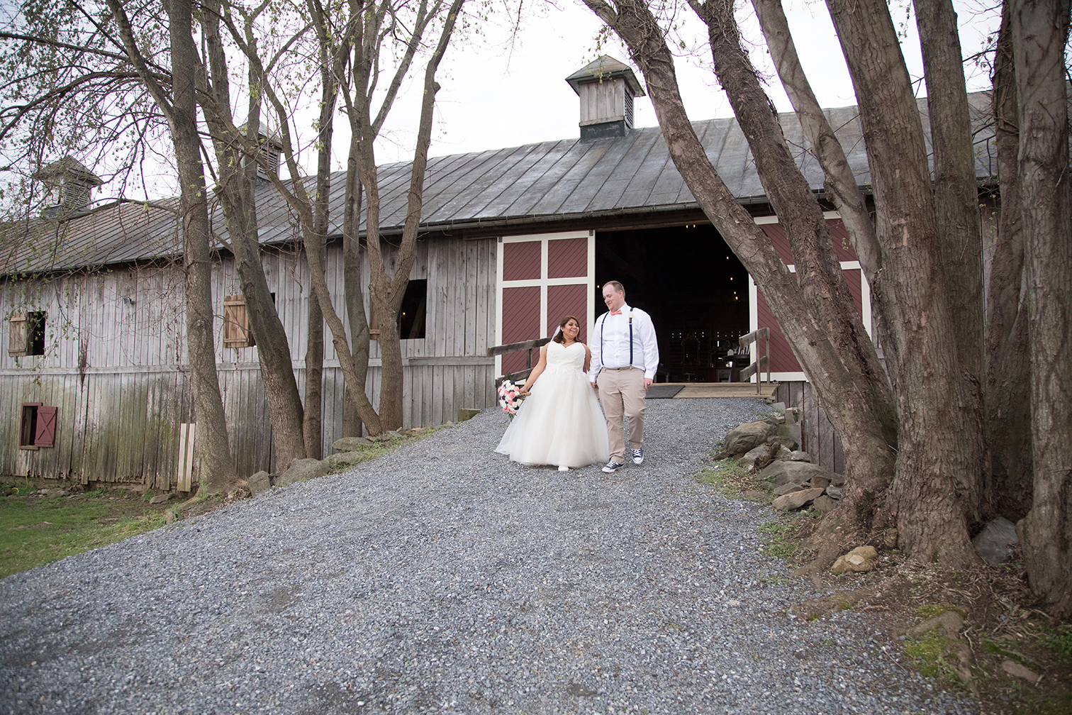 couple walking hand in hand by barn
