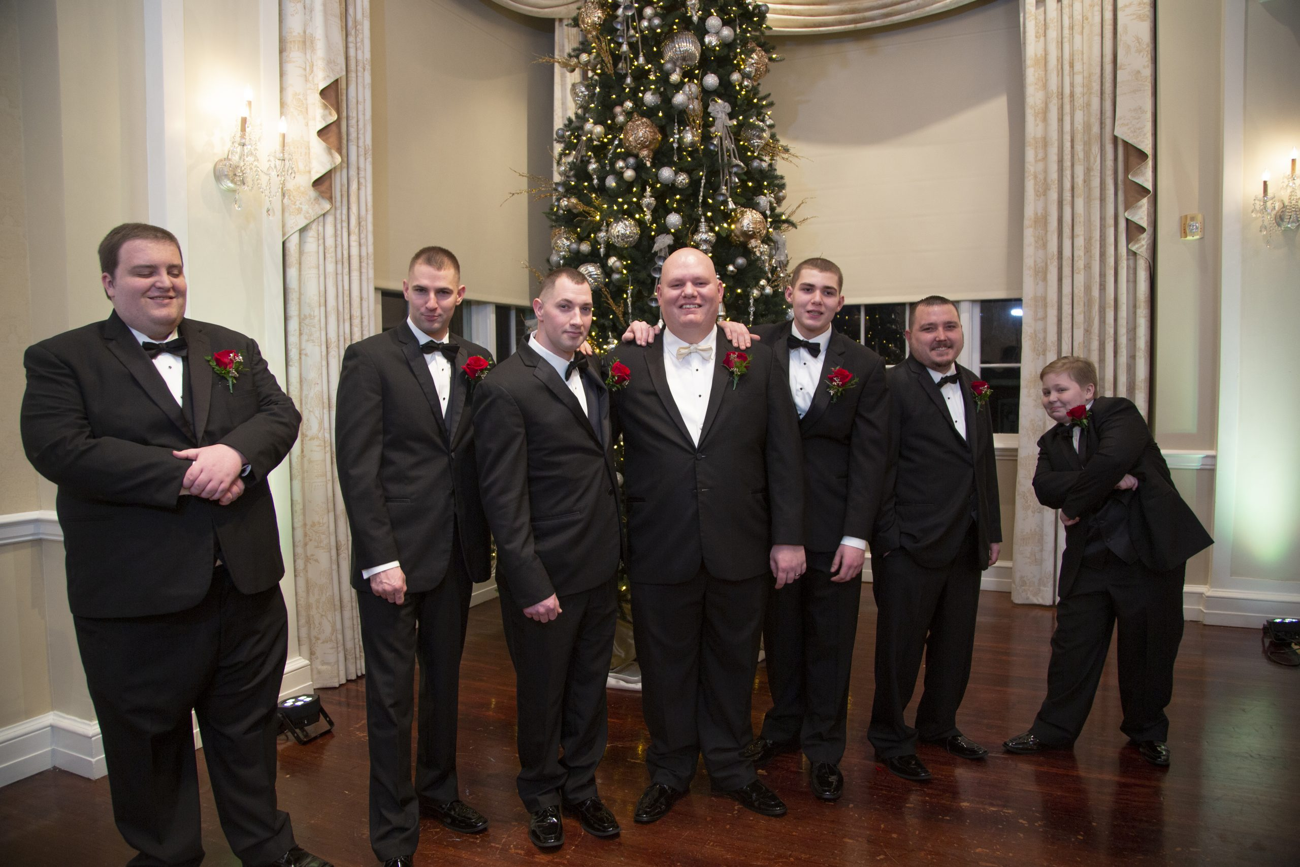 groom and groomsmen by christmas tree. George Washington hotel Christmas wedding