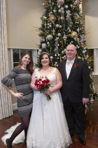 photographer posing with George Washington Hotel Christmas wedding couple.