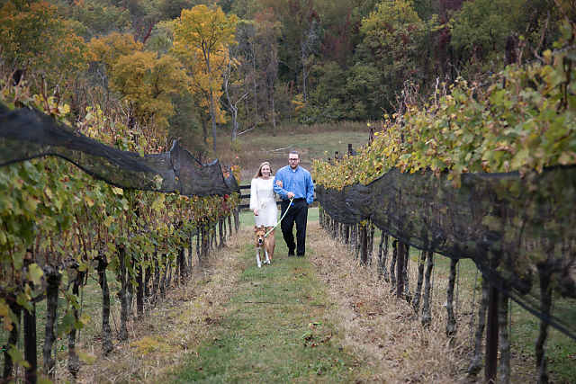 couple walking through grape vines at doukenie vineyard